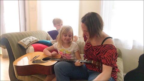 アメリカ・バージニアから届いたQactusを使ってギターを弾く少女の写真